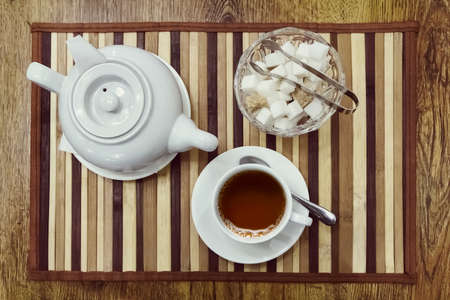 Top view of a cup of tea, teapot and sugar bowl on a wooden background