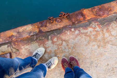 A guy with a girl in jeans and sneakers stands on a rusty pier. Stock Photo