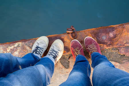 A guy with a girl in jeans and sneakers stands on the edge of a rusty pier. Stock Photo