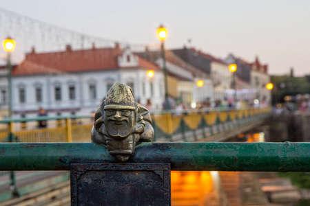 Uzhgorod, Ukraine, August 29, 2017: Mini sculpture of Mikolajczyk, the Santas helper on the handrail of the bridge on the background of the evening city Editorial