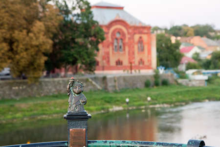 Uzhgorod, Ukraine, August 29, 2017: Mini sculpture of lighthouse Statue of liberty on the handrail of the bridge on the background of the evening city Editorial