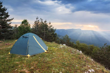 Tourist tent in the camping at the top of the mountain at dawn Stock Photo
