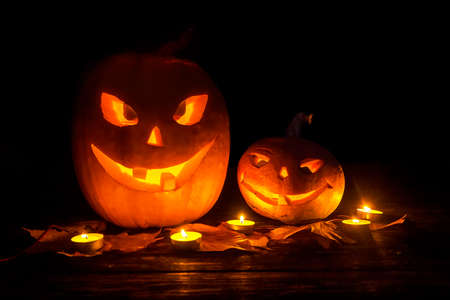 Two pumpkin jack lantern with smiles carved on Halloween with a candle backlight Stock Photo