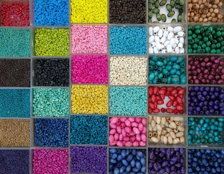 Background of colorful bright beads in boxes, set for needlework Stock Photo