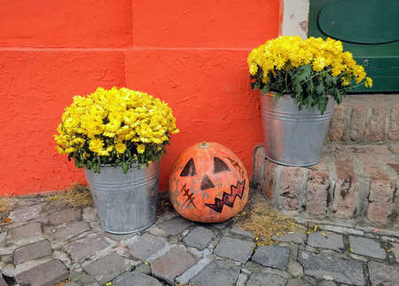 The entrance to the home decorated with pumpkin and yellow chrysanthemums in buckets to Halloween Stock Photo