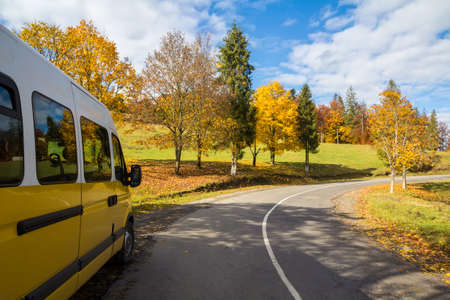 Yellow bus on the turn of autumn road outside the city