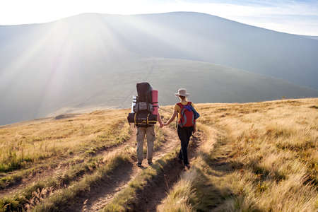 A young man with a girl walk in the mountains together, towards the sun,  holding hands