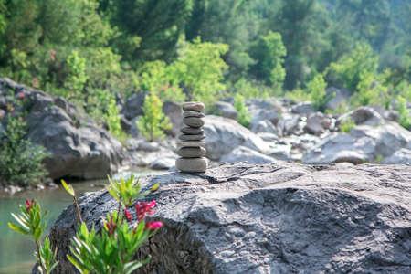 Stones pyramid on rock symbolizing stability, zen, harmony, balance.