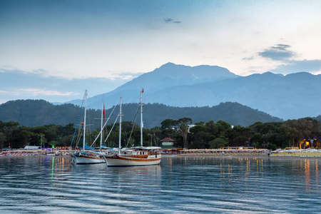 Yachts near the shore of the resort city in the evening, against the backdrop of the silhouette of the mountains Stock Photo