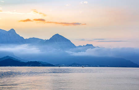 Silhouettes of mountains by the sea coast in the rays of sunset Stock Photo