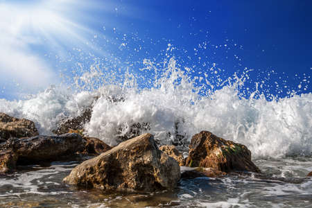 Splashing sea water on rocks isolated on a bright blue sky background Stock Photo