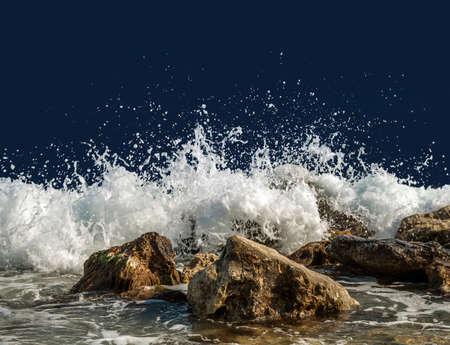 Splashing sea water on rocks isolated on a dark blue background Stock Photo