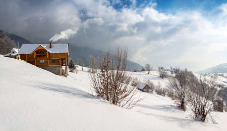 Winter scene, wooden cozy chalet in the mountains with smoke from the chimney