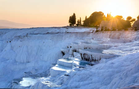 Pools of Pamukkale in Turkey in sunset, contains hot springs and travertines, terraces of carbonate minerals left by the flowing water.