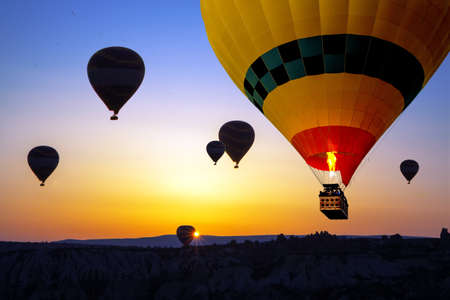 Yellow hot air balloon close-up in the sky of Cappadocia at sunrise