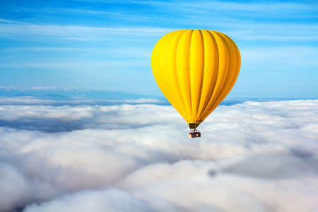 A lonely yellow hot air balloon floats above the clouds. Concept leader, success, loneliness.