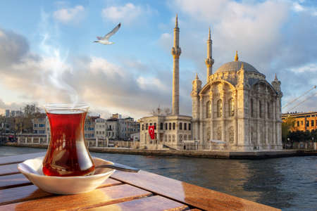 A cup of Turkish tea in a traditional glass against the background of the Medgidiye Mosque in Istanbul