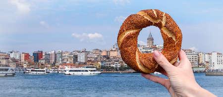 Traditioneller türkischer Bagelsimit in einer weiblichen Hand auf dem Hintergrund des Panoramas von Istanbul und des Galata-Turms, horizontales Banner