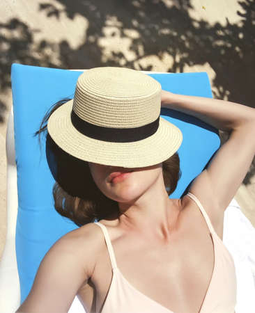 The girl sunbathes in a lounge chair near the pool, covering her face with a hat