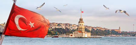 Panorama of Istanbul with Maiden Tower, kiz kulesi, at skyline and seagulls over the sea, wide landscape with the Turkish flag in the foreground, travel background for billboard