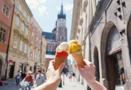 Womens hands with ice cream on the background of the city sights Mariatsky church in the historical center of Krakow, Poland, Europe, a famous tourist place