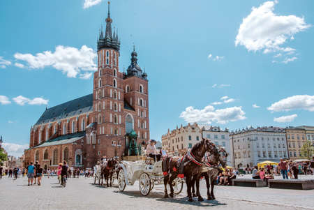 Krakow, Poland, July 15, 2019: Old-fashioned carriage with horses and a driver At Old Town Square In Summer Day, St. Marys Basilica Famous Landmark On Background, Church of Our Lady Assumed into Heav