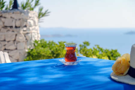 Turkish tea in a traditional glass in the shape of a tulip on a bright sunny day against the background of the Mediterranean Sea