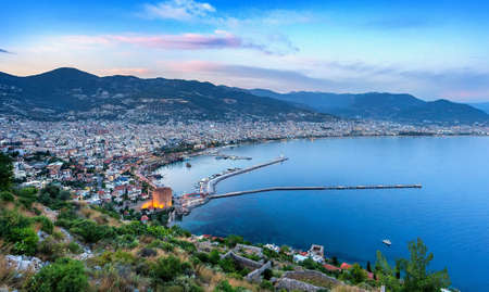 Panoramic evening top view of the bay of the Mediterranean Sea and cityscape with the old historic tower, Alanya, Turkey