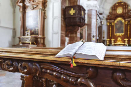 Open the prayer book on the bench in the church