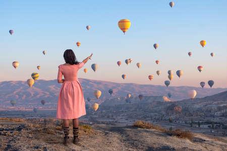 Hot air balloons over Cappadocia, a girl in a pink dress shows a balloon. 스톡 콘텐츠