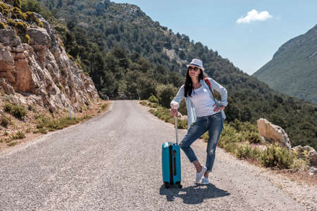Girl traveler in nature with a suitcase