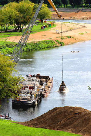 digger: digger bucket deepens the bottom of the shallow river
