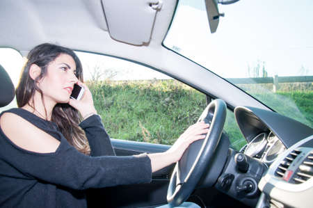 undisciplined: female driver with his smart phone in a sunny day Stock Photo