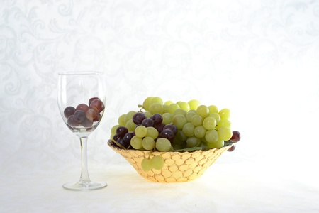 Wine glass with red grapes beside a bowl of green and red grapes Stok Fotoğraf