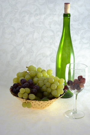 Green wine bottle with glass with red grapes and bowl of red and green grapes Stok Fotoğraf