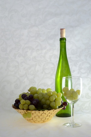 Green wine bottle with cork and bowl of green and red grapes