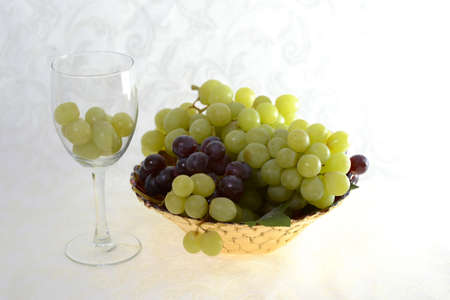 Wine glass with green grapes and  bowl of green and red grapes on a white damask background Stok Fotoğraf
