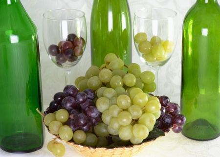 3 wine green wine bottles with glasses and grapes