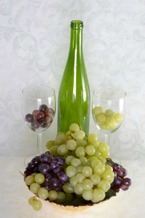 Green wine bottle with two wine glasses and a bowl of grapes Stok Fotoğraf