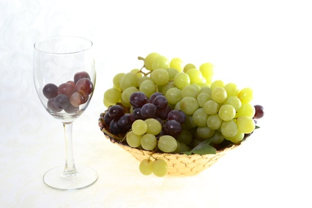 Bowl of red and green grapes with glass of red grapes Stok Fotoğraf