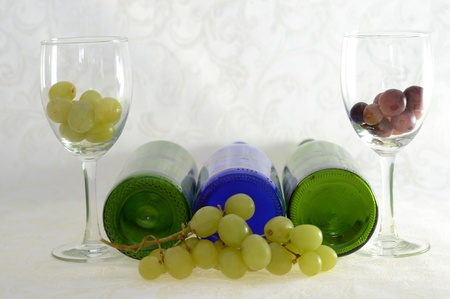 Three wine bottles lying down with two wine glasses