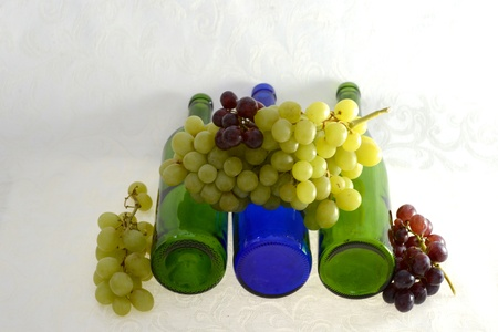 Four wine bottles laying down with red and green grapes