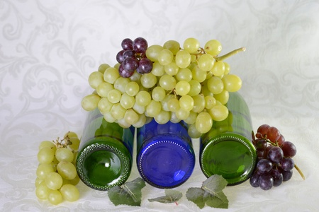 Four wine bottles laying down with red and green grapes and grape leaves Stok Fotoğraf