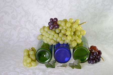 Green and blue wine bottles lying down with red and green grapes Stok Fotoğraf