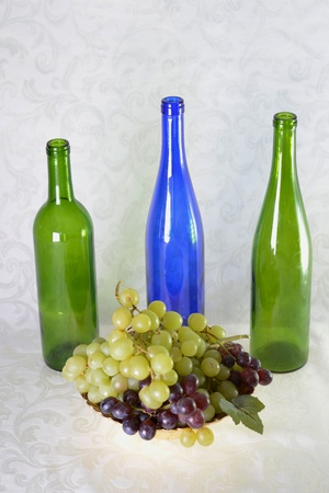 Three wine bottles, green and blue with bowl of grapes with grape leaves