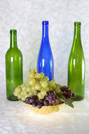 Three wine bottles, green and blue with bowl of grapes