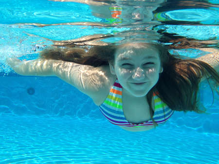 Little girl having fun swimming in the pool Banco de Imagens
