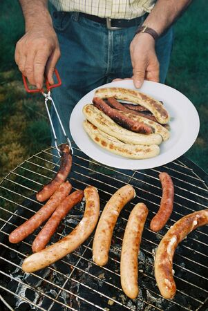 Sausages on Barbecue BBQ grill hold on plate