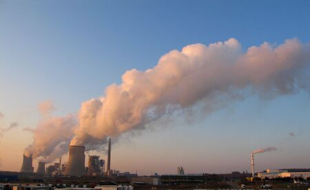 Coal fired power plants generanting smokes at the sunset