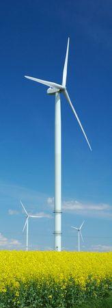farm of windturbines close to rape field France